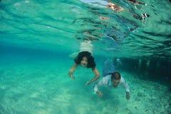 Undervattens- härlig älskvärd kyss för brud och för brudgum Arkivfoto