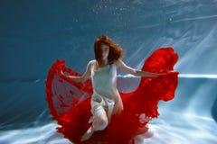 Undervattens- i pölen med det mest rena vattnet Härlig ung flicka i en scharlakansröd klänning och ett flödande hår Royaltyfria Foton