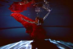 Undervattens- i pölen med det mest rena vattnet Härlig ung flicka i en scharlakansröd klänning och ett flödande hår Arkivbild