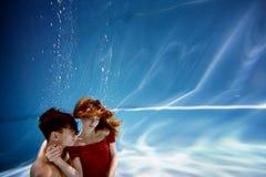 Undervattens- i pölen med det mest rena vattnet par som kramar att älska Känslan av förälskelse och closeness slapp fokus royaltyfri bild