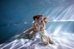 Undervattens- i pölen med det mest rena vattnet par som kramar att älska Känslan av förälskelse och closeness slapp fokus arkivfoton