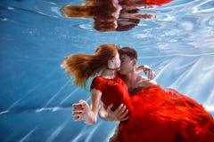 Undervattens- i pölen med det mest rena vattnet par som kramar att älska Känslan av förälskelse och closeness slapp fokus royaltyfria foton