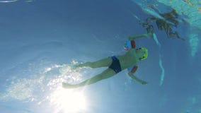 Undervattens- längd i fot räknat av en pojkesimning i en pöl, bärande armbindlar stock video