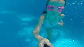 Undervattens- lycklig härlig flicka i simbassängen som har gyckel lager videofilmer