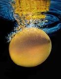 Undervattens- orange frukt med vattenbubblor Royaltyfri Foto