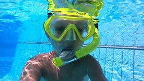 Undervattens- sikt av en pojke som omkring bedrar lager videofilmer