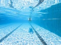 Undervattens- sikt av mannen i simbassäng arkivfoto