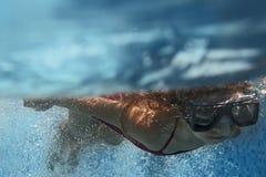 Undervattens- simning för blond barnflicka i blå pöl arkivbilder