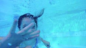 Undervattens- skott av två ungar som dyker i en simbassäng stock video