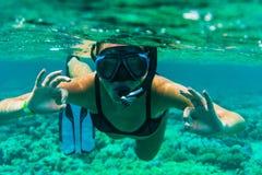 Undervattens- snorkla för kvinna med att göra en gest ok simning i havet royaltyfri foto