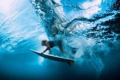 Undervattens- surfarekvinnadyk Surfgirl dyk under stor våg royaltyfri foto