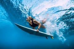 Undervattens- surfarekvinnadyk Surfgirl dyk under våg royaltyfri bild