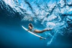 Undervattens- surfarekvinnadyk Surfgirl dyk under våg fotografering för bildbyråer