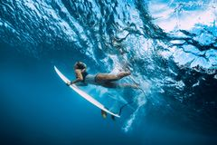 Undervattens- surfarekvinnadyk Surfgirl dyk under våg royaltyfria bilder