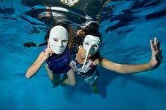 Undervattens- teater Två ovanliga flickor simmar och spelar undervattens- i pölen på en blå bakgrund i vita maskeradmaskeringar royaltyfria bilder