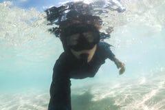 Undervattens- ung man som snorklar ha gyckel i havet fotografering för bildbyråer