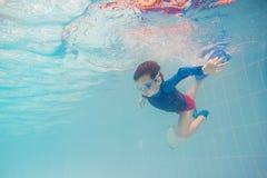 Undervattens- ung pojkegyckel i simbassängen med skyddsglasögon Gyckel för sommarsemester royaltyfri foto