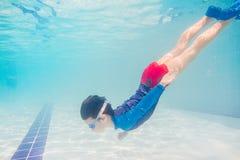 Undervattens- ung pojkegyckel i simbassängen med skyddsglasögon Gyckel för sommarsemester Fotografering för Bildbyråer