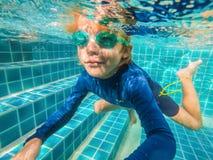 Undervattens- ung pojkegyckel i simbass?ngen med skyddsglas?gon Gyckel f?r sommarsemester royaltyfri fotografi