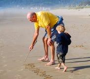 Undervisande bokstäver till småbarnutbildning på stranden arkivfoto