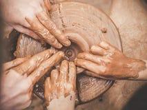 Undervisande carftmans för krukmakeri som A händer vägleder en barnhand som visar hur man kastar en lerakruka på ett keramikerhju royaltyfria bilder