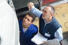 Undervisande deltagare i utbildning för mekaniker i garageseminarium arkivbilder