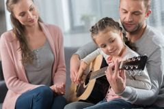 Undervisande dotter för fader hur man spelar den akustiska gitarren, medan modern sitter med dem arkivbild