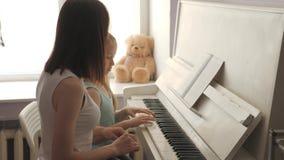 Undervisande dotter för moder som hemma spelar pianot arkivfilmer