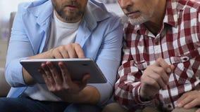 Undervisande fader för son hur man använder minnestavlan, online-arbete för moget folk som är frilans- stock video