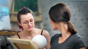 Undervisande kvinnastudent f?r yrkesm?ssig kvinnlig m?lare som skissar bollen p? seminariummedeln?rbilden stock video