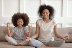 Undervisande meditation för sund afrikansk moder att sitta med dottern på soffan royaltyfria bilder