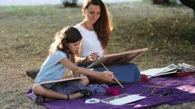 Undervisning för ung kvinna som drar en flicka på parkera i solig sommardag arkivfilmer
