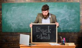 Undervisningelever hans yrkesmässiga ockupation Läraren eller skolarektorn välkomnar inskriften tillbaka till skolan lärare arkivfoton