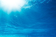 Underwater. View looking up towards surface with bright sun rays filtering down stock photography