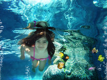 Underwater. Little girl going underwater with 3d coral fishes Stock Photo