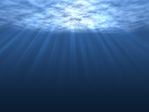 Underwater. An underwater scene with sunrays shining through the water's glittering and moving surface Stock Images