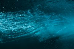 Underwater barrel wave and surfer in tropical sea in Oahu. Royalty Free Stock Photo