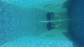 Underwater - beautiful woman in blue dress falls in swimming pool. Underwater. Beautiful woman in long blue dress falls down into the swimming pool. Charming stock video