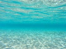 Underwater blue ocean background with sandy sea bottom