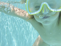 Underwater bubbles. Boy blowing bubbles underwater in the swimming pool Stock Image