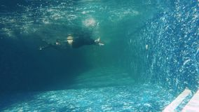Businessman swims under water in slowmotion in swimming pool. Underwater. Businessman in suit falls down under water in blue swimming pool. The guy in suit stock video footage