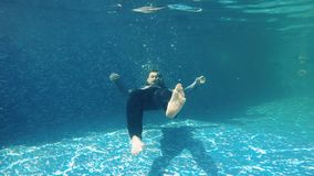Businessman swims under water in slowmotion. Underwater. Businessman in suit swims under water in blue swimming pool. The guy in suit creates air bubbles around stock video footage
