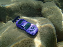 Underwater car. Small violet car toy parked on the stone under the sea Stock Photos
