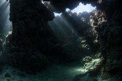 Underwater Cavern. Light pours into a shallow underwater cavern in the Solomon Islands. This area is the easternmost part of the Coral Triangle and houses an stock image