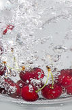 Underwater cherries. Cherries inside the glass full of water Royalty Free Stock Images