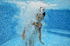 Underwater child jumps to swimming pool Royalty Free Stock Images
