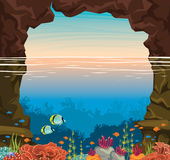 Underwater coral reef, fish, sea, sunset sky, cave. Cartoon coral reef with school of fishes and sea cave under the sunset sky. Underwater sea wildlife. Vector Royalty Free Stock Photo
