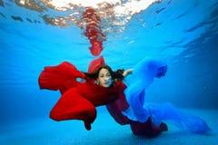 Underwater della ragazza impigliato in rosso e tessuti blu ed esaminare la macchina fotografica Fotografia Stock