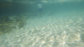 Underwater exploration. A moving shot under a turquoise sea water. Light reflection touches the sea surface. A pan to right showed a diver wearing white diving stock video