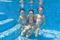 Underwater family in swimming pool. Mother with two kids swimming underwater in pool Royalty Free Stock Image